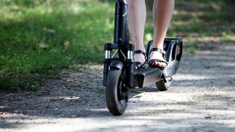 E-Scooter - Circ - Beine - Sandalen - Füße - Person - Weg - Wiese